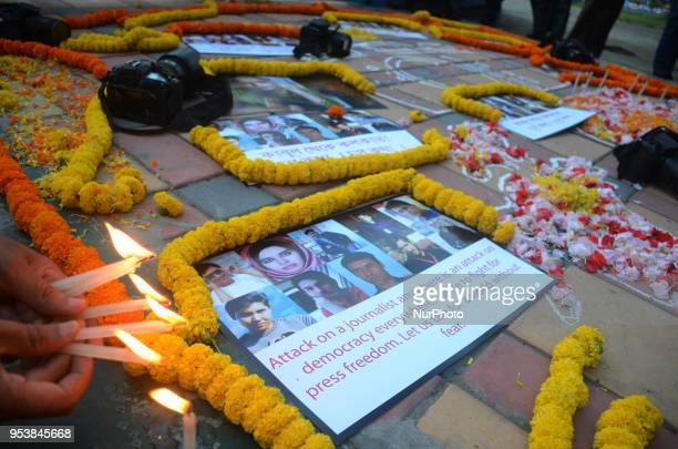 An Indian photojournalist lights a candle during a candle light vigil to pay tribute for ten Afghan journalists who were killed in an explosion while...