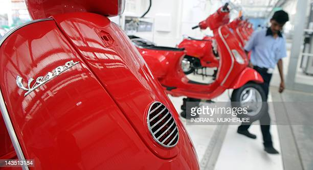 An Indian Piaggio employee inspects Vespa scooters on a production line at the newly inaugurated Vespa plant at Baramati some 150 kms south east of...