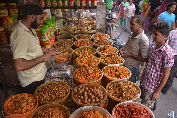 An Indian pickle vendor serves customers at his shop in a vegetable market of Amritsar on July 2 2015 Bad weather has meant this year`s mango crop...