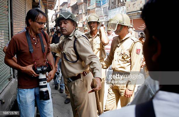 An Indian police officer confronts a photojournalist during clashes with antiIndia protestors on August 30 2010 in Srinagar the summer capital of...