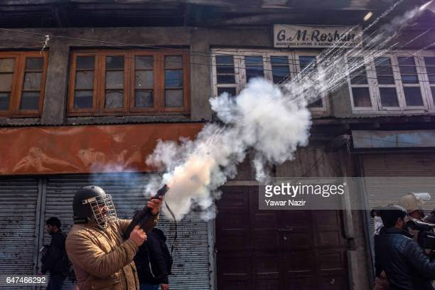 An Indian police officer fires a teargas shell towards Kashmiri Muslim protesters during an anti India protest on March 03 2017 in Srinagar the...