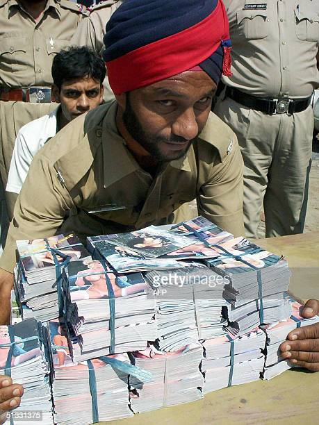 An Indian police officer handles pornographic magazines seized during a raid in Patiala some 275 Kms north of New Delhi 21 September 2004 Police...