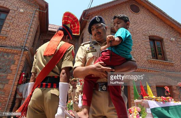 An Indian police officer hold the son of Station House Officer Arshad Khan during his wreath laying ceremong in district police lines in...