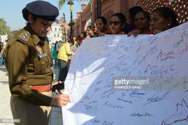 An Indian police officer place her signatures during an awareness campaign 'save the girl child' on the eve of International Women's Day in Amritsar...