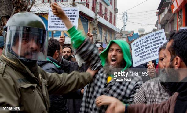 An Indian police officer stop Members of Joint Resistance Leadership an amalgamation of Kashmiri proindependence groups hold placards during a...