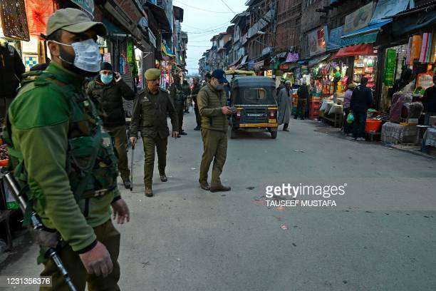 An Indian police officer uses a drone while patrolling a street following an attack which killed two policemen last week, in Srinagar on February 24,...