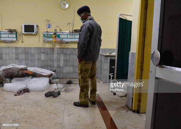 An Indian police official covers up the dead body of victim of NTPC boiler explode in Jeevan Jyoti hospital Unchahaar on November 2 2017 26 people...