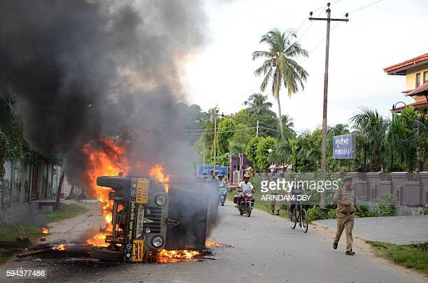 An Indian police official runs past a burning vehicle in Agartala on August 23 after violence flared in the northeastern Indian city between...