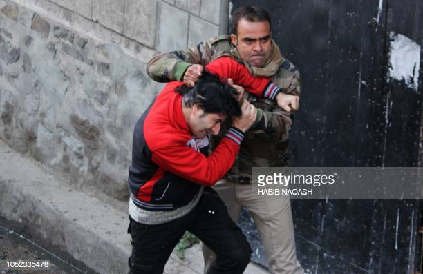 TOPSHOT An Indian police official scuffles with a Kashimiri youth during a clashes near the site following a gun battle between suspected militants...