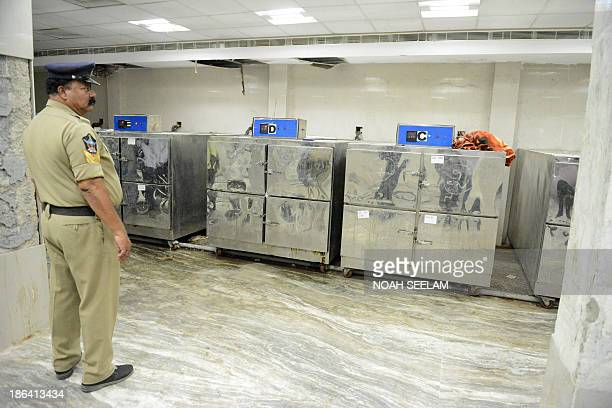 An Indian police official stands inside the mortuary of The Osmania General Hospital in Hyderabad on October 31 as relatives prepare to identify...