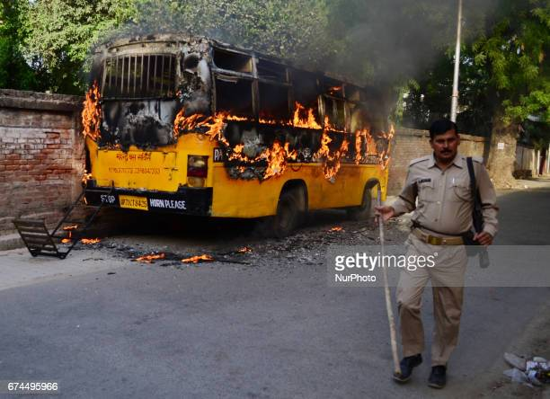 An Indian police official walkes near a burining bus set by students in Allahabad on April2017 Allahabad University witnessed large scale violence...