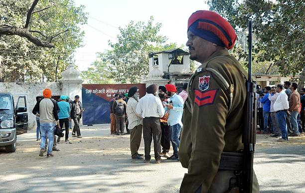 An Indian police personnel and onlookers stand near the gate of the Nabha maximumsecurity jail in Nabha in the state of Punjab on November 27 2016 At.
