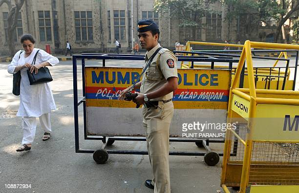 An Indian policeman adjusts barricades as he stands guard outside the high court where Mohammed Ajmal Amir Kasab's appeal is being held in Mumbai on...