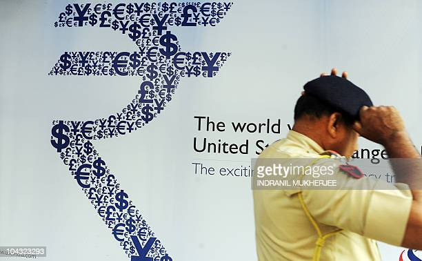 An Indian policeman adjusts his cap as he walks past a collage of the new Indian rupee symbol made with signs of the US dollar the yen the pound and...