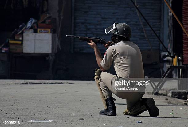 An Indian policeman aims his weapon towards Kashmiri Muslim protesters during a protest over the killing of a civilian by Indian army on Tuesday in...
