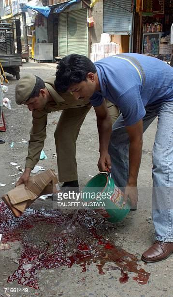 An Indian policeman and a bystander clean a bloodstained pavement at Kukar Bazar in Srinagar, 17 August 2006, following an attack by suspected...
