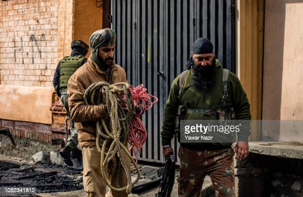 An Indian policeman carrying ropes after a gun battle between Indian government forces and Kashmiri rebels on October 17 2018 in Srinagar the summer...
