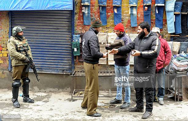 An Indian policeman checks the identity document of a Kashmiri civilian during a cordon and search operation at Lal Chowk in Srinagar on January 5...