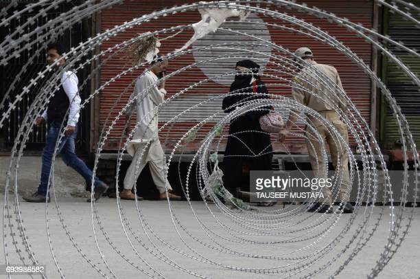 An Indian policeman closes a barbed fence wire after letting Kashmiri residents pass through a checkpoint during a curfew and strike called following...