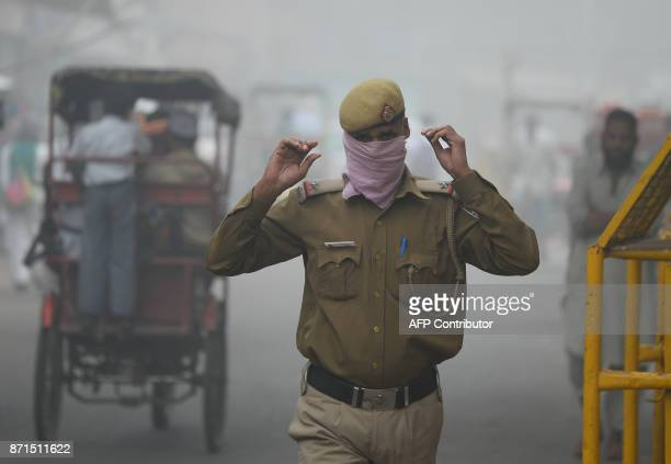 An Indian policeman covers his face with handkerchief as he walks amid heavy smog in New Delhi on November 8 2017 Delhi shut all primary schools on...