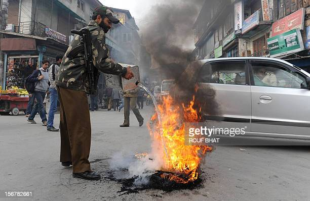 An Indian policeman extinguishes a burning tyre after the news that Pakistanborn Mohammed Kasab the sole surviving gunman from the 2008 Mumbai...