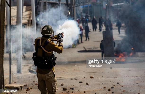 An Indian policeman fires a teargas shell at Kashmiri protesters during clashes between Indian government forces and Kashmiri Muslims near the site...