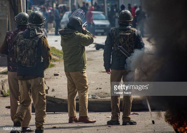 An Indian policeman fires metal pellets at Kashmiri protesters during clashes between Indian government forces and Kashmiri Muslims near the site...