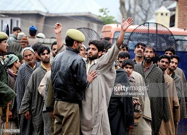 An Indian policeman frisks Indian Kashmiri voters outside a polling station in Bandipora south of Srinagar on November 17, 2008. Indian Kashmir voted...