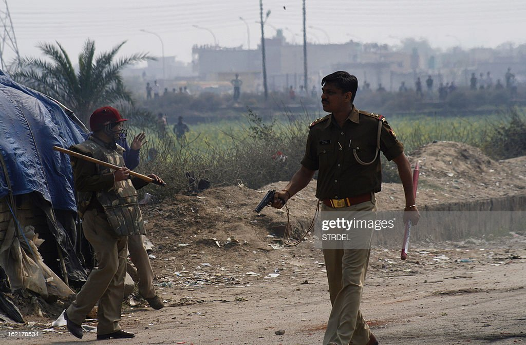 An Indian policeman holds his gun during a trade union strike in Nodia on the outskirts of New Delhi on February 20, 2013. Cars were burnt and factories were stoned when violence broke out at the all-India trade union strike. Millions of India's workers walked off their jobs in a two-day nationwide strike called by trade unions to protest at the 'anti-labour' policies of the embattled government. Financial services and transport were hit by the strike called by 11 major workers' groups to protest at a series of pro-market economic reforms announced by the government last year, as well as high inflation and rising fuel prices.