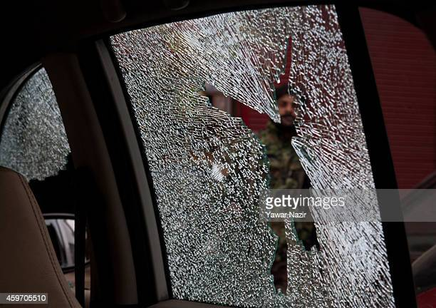 An Indian policeman is seen through a damaged car screen attack in the city centre on November 29 in Srinagar the summer capital of Indian...