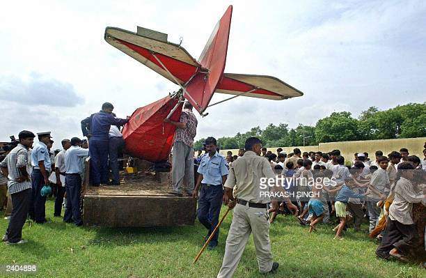 An Indian policeman keeps young children away as Indian Air Force personnel load the wreckage of a microlight aircraft on to a truck near Hindon air...