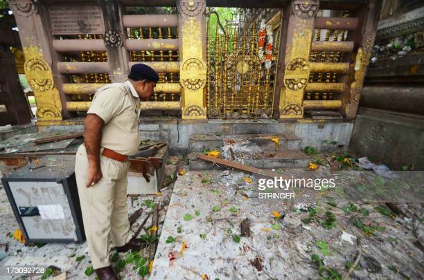 An Indian policeman looks at debris left after several low intensity explosions took place at at the Bodh Gaya Buddhist temple complex injuring two...