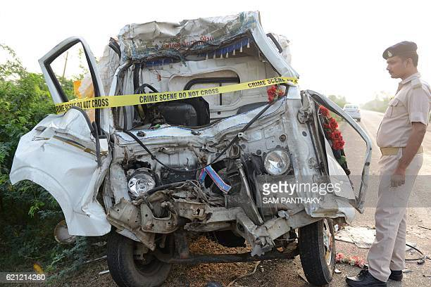 An Indian policeman looks at the remains of a passenger van that collided with a truck in a crash that killed 14 pilgrims near Valthera village some...