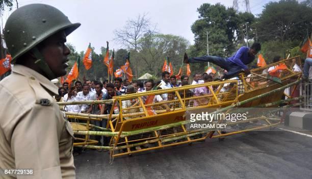 An Indian policeman looks on as Bharatiya Janata Party activists break through a barricade across a street in Agartala on March 4 during a rally held...