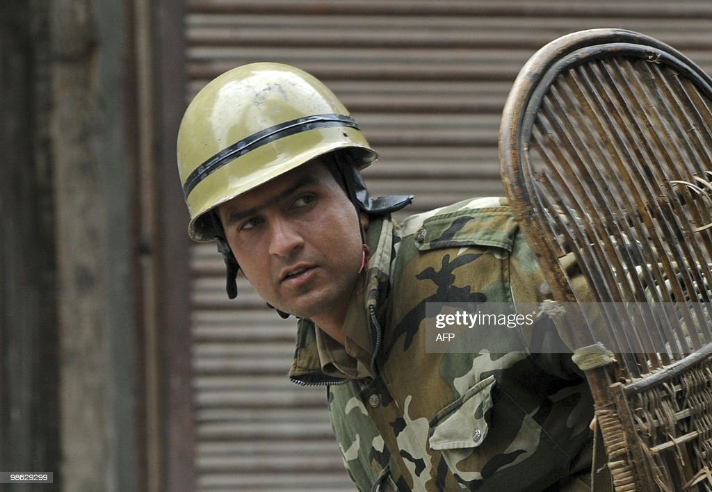 An Indian policeman looks on during a clash with Kashmiri protestors in Srinagar on April 23, 2010. Police detained activists including the chairman of Jammu and Kashmir Liberation Front (JKLF) Yasin Malik during a protest against death sentences handed to three members of a Kashmiri group that bombed a New Delhi market in 1996. Life in Indian Kashmir was crippled by a one-day strike to protest the death sentences. On April 13, one person was killed and 24 hurt during a strike called to protest the initial convictions for the bombing, which left 13 dead and dozens injured in New Delhi's Lajpat Nagar shopping area. Anti-India insurgents have waged a two-decade fight against rule by New Delhi in the Himalayan region that has left more than 47,000 people dead, according to the official count.Seperatists put the toll twice as high. AFP PHOTO/Tauseef MUSTAFA