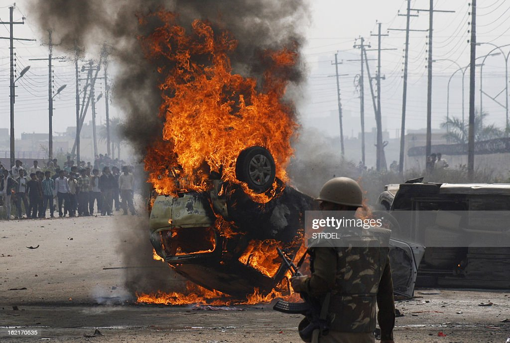 An Indian policeman looks on near a burning car during a trade union strike in Nodia on the outskirts of New Delhi on February 20, 2013. Cars were burnt and factories were stoned when violence broke out at the all-India trade union strike. Millions of India's workers walked off their jobs in a two-day nationwide strike called by trade unions to protest at the 'anti-labour' policies of the embattled government. Financial services and transport were hit by the strike called by 11 major workers' groups to protest at a series of pro-market economic reforms announced by the government last year, as well as high inflation and rising fuel prices.