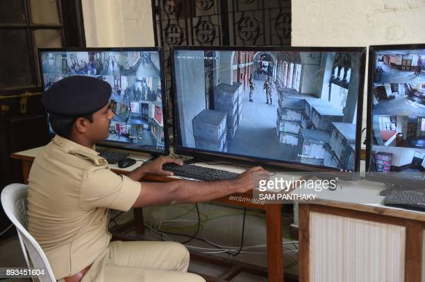 An Indian policeman monitors CCTV footage of strong rooms contanining Electronic Voting Machines and other electoral material at a centre in...