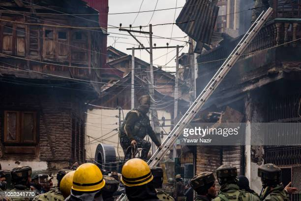 An Indian policeman on a ladder enters a residential house to retrieve the body of their comrade killed in a gun battle between Indian government...