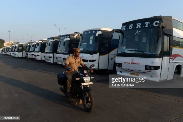 An Indian policeman patrols past buses parked at a terminal in Chennai on February 16 2018 India suffers severe water shortages that cause frequent...