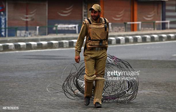 An Indian policeman pulls a barbed wire fence during a curfew in the Maisuma locality of Srinagar on May 2 2014 Parts of Kashmir remained under...