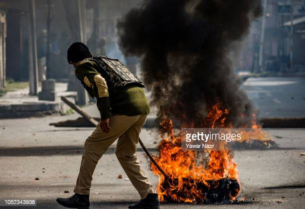 An Indian policeman removes a burning tire left by Kashmiri Muslims near the site of gun battle following clashes between Indian government forces...