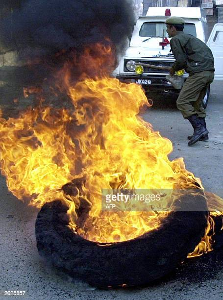 An Indian policeman runs by burning tyres 22 October 2003 during a protest against the arrest of influencial proindependence leader Yasin Malik in...