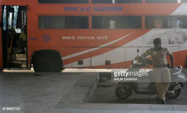 An Indian policeman sits next to bus parked at a terminal in Chennai on February 16 2018 India suffers severe water shortages that cause frequent...