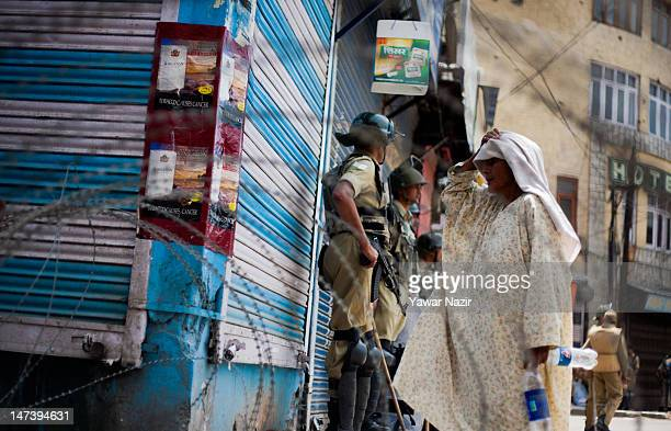 An Indian policeman speaks to an elderly Kashmir woman during an undeclared curfew on June 29 2012 in Srinagar the summer capital of Indian...