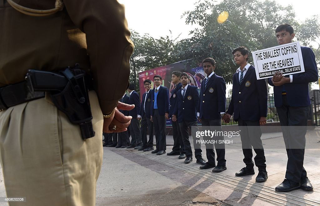 An Indian policeman stand guards as school children make human chain