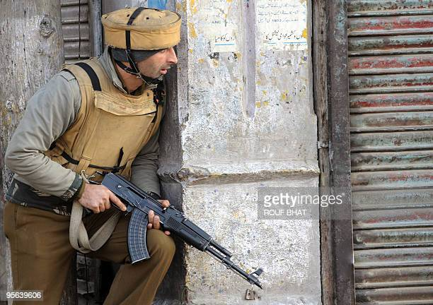 An Indian policeman stands alert during an encounter in Srinagar on January 6 2010 Suspected Muslim militants opened fire in the main market area of...