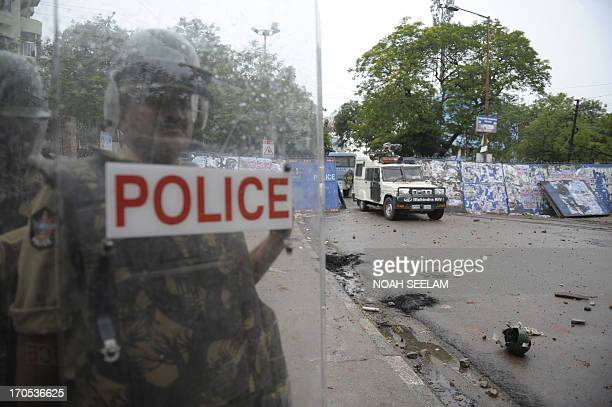 An Indian policeman stands behind his shield during a protest by Telangana Joint Action Committee activists in Hyderabad on June 14 2013 The TJAC and...
