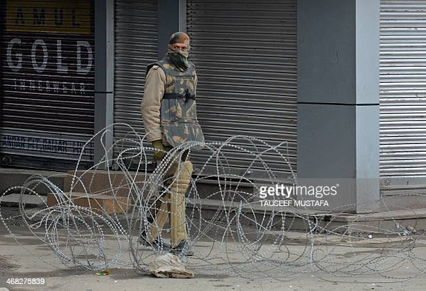 An Indian policeman stands guard alongside a barbed wire roadblock in Srinagar on February 10 2014 Political groups opposed to Indian rule in the...