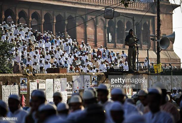 An Indian policeman stands guard as Indian Muslims offer the early morning Eid alFitr prayer at the Jama Masjid mosque in New Delhi on September 21...