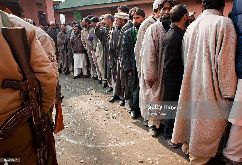 An Indian policeman stands guard as Kashmiri Muslim village heads wait in queues to enter polling station to cast their vote during state's legislative council election on December 03, 2012 in Budgam, west of Srinagar, Indian Administered Kashmir. Village heads in Indian-administered Kashmir voted for their representatives in the state's legislative council after 38 years today. These grass root workers are represented by four people in the council- the lower house of Kashmir assembly. This year the village heads were attacked by unidentified gunmen in the conflict torn region. Many resigned from their post after at least 10 village heads were killed in attacks. Today's polling saw long queues despite the resistance leadership calling for a boycott. But the biggest militant group in the region- the Hizbul Mujahideen- had refrained from calling a boycott saying the polling was necessary for daily administration of the state.